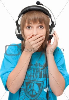 Beautiful girl in earphone closes mouth by hand