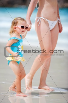 Mother and daughter walking at beach