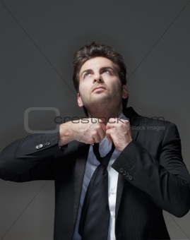 businessman in suit loosening up his tie - isolated on gray