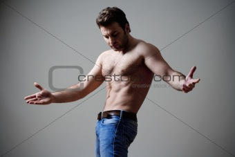 young shirtless musculous man in jeans - isolated on gray