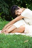 Sensual young brunette sitting on grass