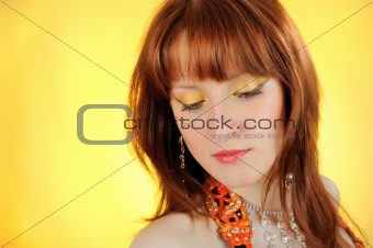 Beautiful woman with golden make-up. yellow background