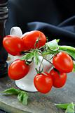 cherry tomatoes and basil in a white gravy boat