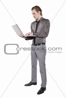 A young man stands with a computer.