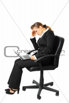 Tiredness modern business woman sitting on chair and using laptop