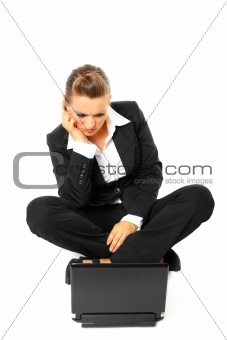 Sitting on  floor bored modern business woman looking in laptop