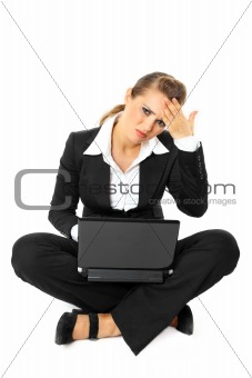 Sitting on  floor modern business woman with headache working on laptop