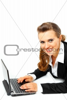 Laying on floor smiling modern business woman using  laptop
