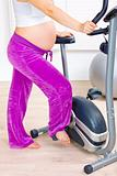 Pregnant female preparing for workout on stationary bicycle. Close-up.