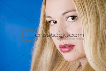 Beautiful young woman with red lips and blond long hair against the blue background.