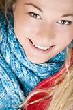 Smiling woman wearing red jacket and blue scarf. Autumn fashion.