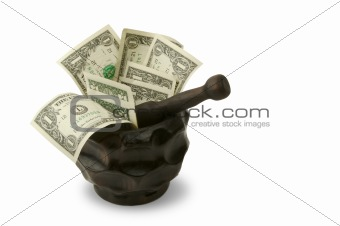 Grinding for Dollars - Wood mortar and pestle containing dollar bills on a white background.