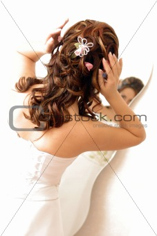 Woman looking at hair in mirror