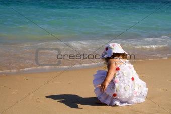 Little girl crouching on the beach
