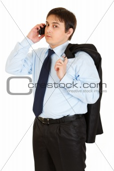 Thoughtful young businessman with jacket on his shoulder talking on mobile phone