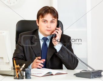 Thoughtful modern businessman talking on phone and making notes in diary