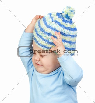 Angry baby taking off a wool cap