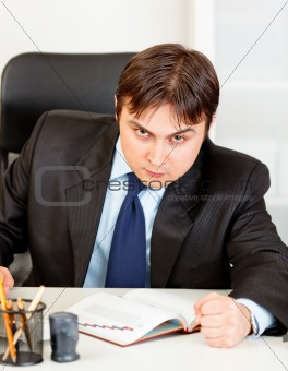 Angry modern businessman banging fist on table