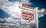 White Foreclosure Home For Sale Real Estate Sign Over Beautiful Clouds and Blue Sky.
