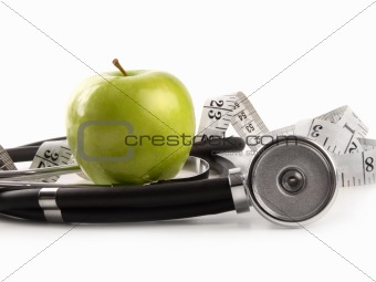 Green apple and measuring tape with stethoscope on white