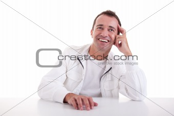 smiling middle-age man sitting at desk on a black background. Studio shot