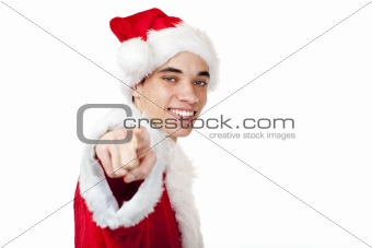 Smiling male teenager dressed as santa claus points with finger