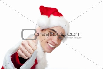 Smiling male santa claus teenager shows thumb up