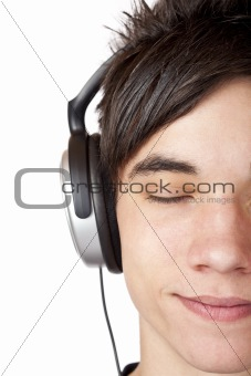 Close-up macro of a male teenager listening to music with headphone