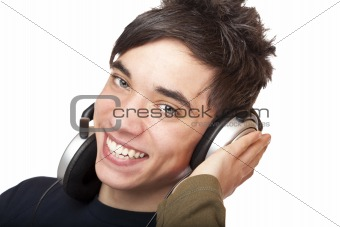 Male Teenager with headphones listens to music and smiles happy