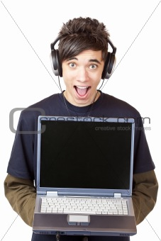 Male Teenager with earphones makes mp3 music download with computer