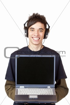 Male Teenager with earphones makes Internet mp3 music download at computer