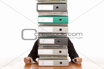Desperate business woman sits behind folder stack