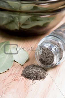 black pepper in shaker and bay leaves