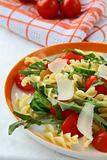 pasta salad with tomatoes and arugula in
