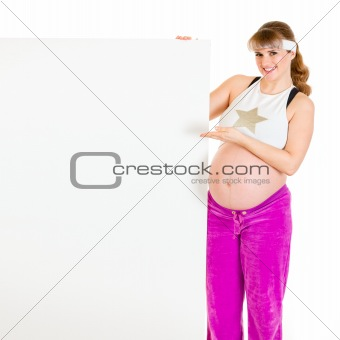 Smiling beautiful pregnant woman pointing on blank billboard
