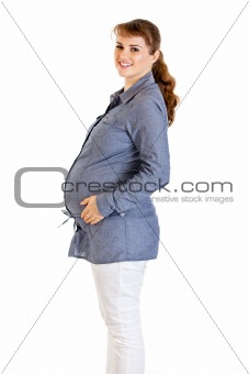 Smiling beautiful pregnant woman holding her tummy isolated on white