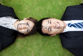 Business couple.happy  businessman and woman Lay on the grass