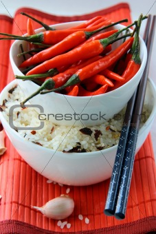 Bowls of uncooked rice and chili peppers