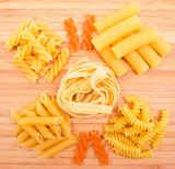 Different kinds of pasta on the wooden background