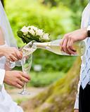 Man fills newly-married couple's glasses with champagne