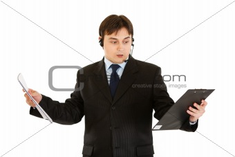 Stressed modern businessman with headset holding documents in hands