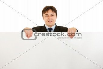 Smiling modern businessman holding blank billboard