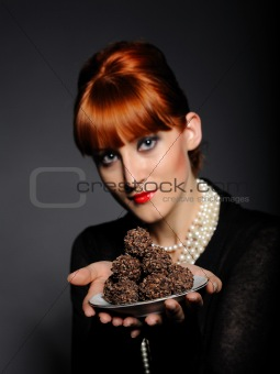 Beautiful elegant fashion woman with chocolate truffle sweets.