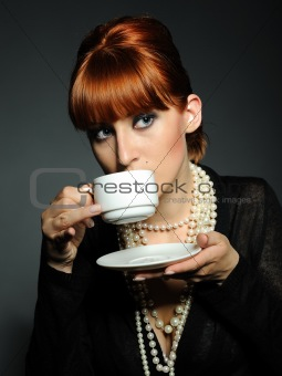 Beautiful aristocratic fashion woman with white pearls drinking