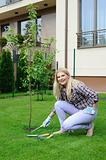 Pretty gardener woman with gardening tools outdoors