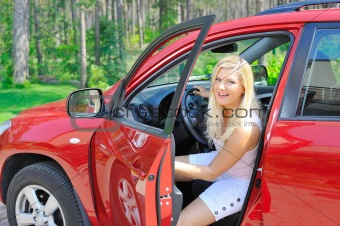 beautiful woman driver in red shiny car opens the door