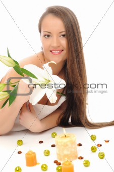 Beautiful woman with pure healthy skin, long hair with a flower