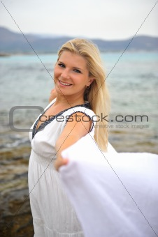 Young beautiful romantic woman in white dress dancing with shawl