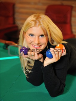 beautiful smiling woman with many billiard balls indoors