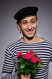Funny emotional romantic sailor man holding rose flowers